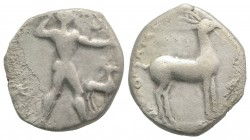 Bruttium, Kaulonia, c. 475-425 BC. AR Stater (22mm, 7.65g, 11h). Nude Apollo walking r., holding branch, holding small running daimon on outstretched ...