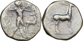 Greek Italy. Bruttium, Kaulonia. AR Stater, c. 475-425 BC. D/ Apollo advancing right, holding branch; small daimon running on Apollo's left arm; to ri...