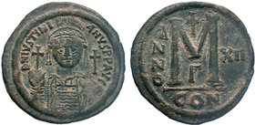 BYZANTINE.Justinian I, AE Follis. Constantinople. 527-565 AD. DN IVSTINIANVS PP AVG, helmeted, cuirassed bust facing holding cross on globe and shield...